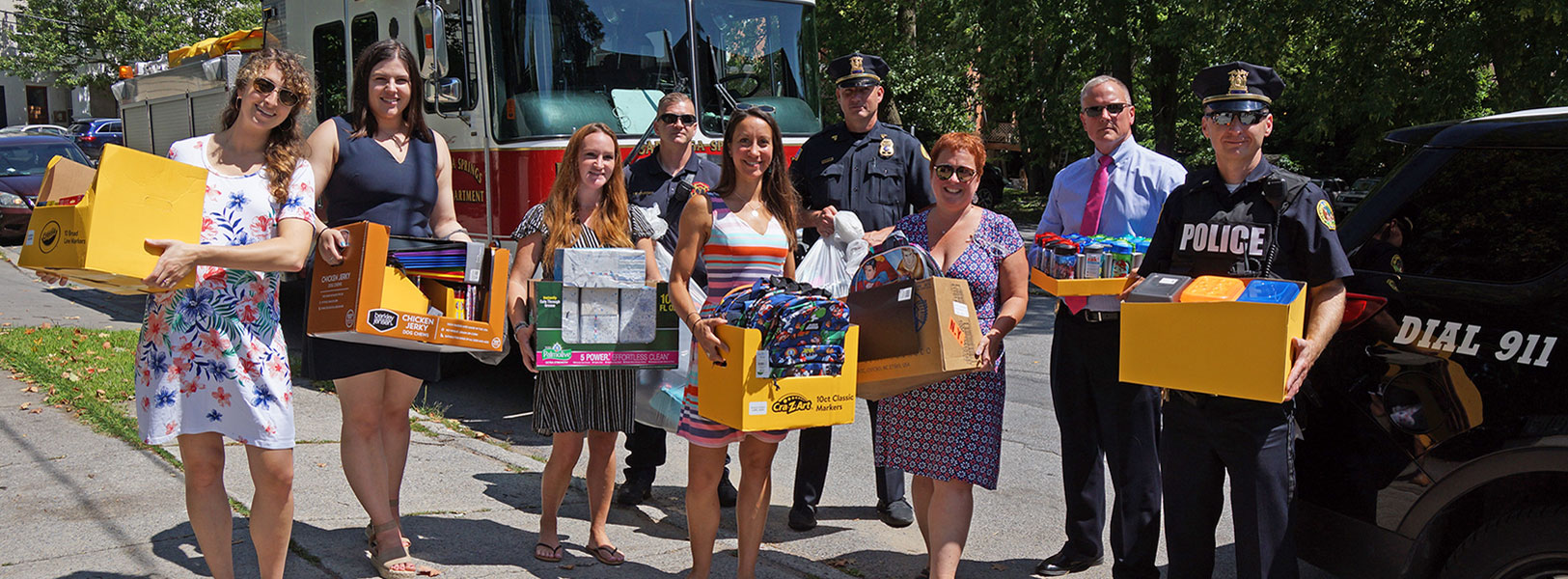 Saratoga Police, Fire Department and Community members holding boxes of donated supplies for Franklin Comunity Center