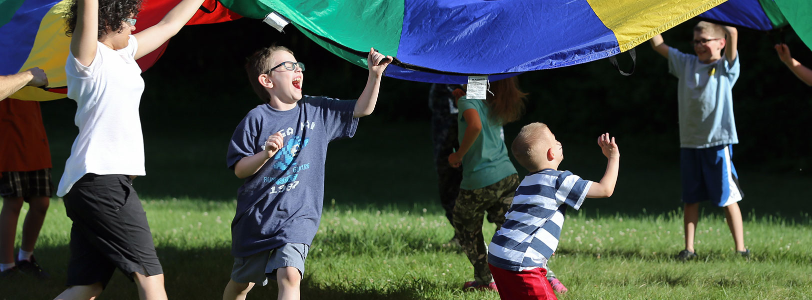 Kids laughing and playing with a colorful parachute