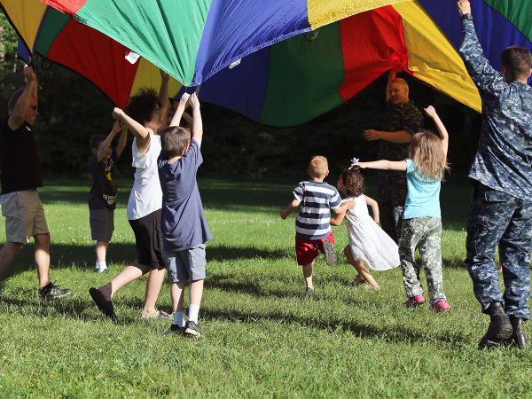 Kids running under parachute